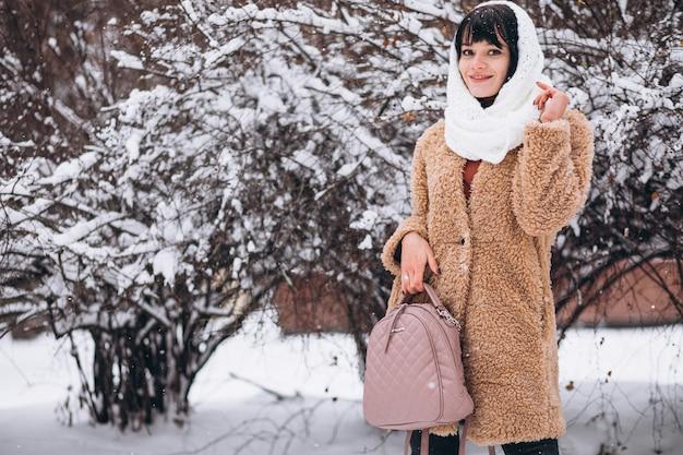 Joven mujer feliz en paños calientes en un parque de invierno Foto gratis
