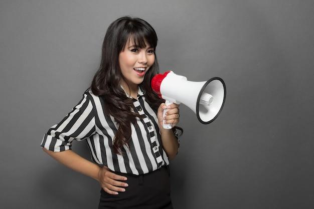Joven mujer gritando con un megáfono Foto Premium