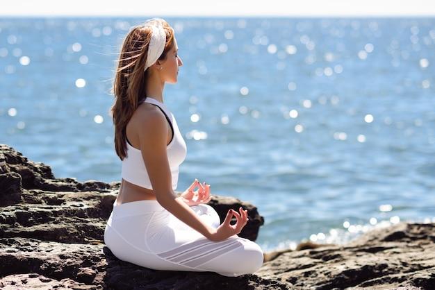 Joven mujer haciendo yoga en la playa con ropa blanca Foto Gratis