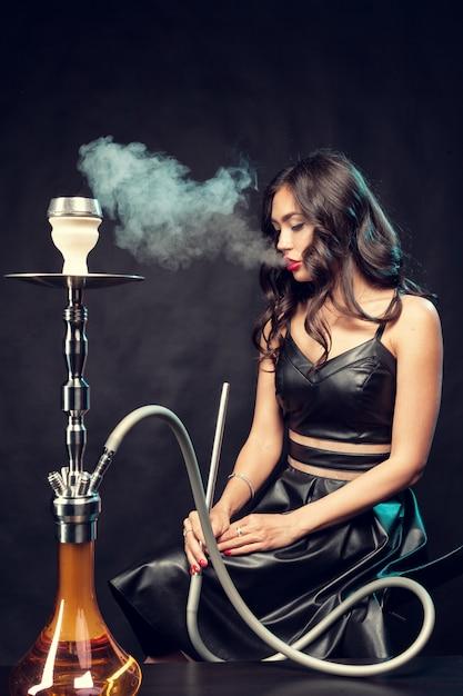 Joven mujer hermosa en vestido negro fumando y exhala cachimba Foto Premium