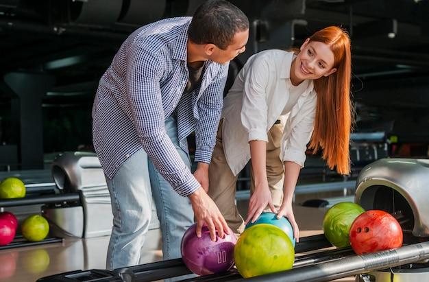 Joven mujer y hombre tomando coloridas bolas de boliche Foto gratis