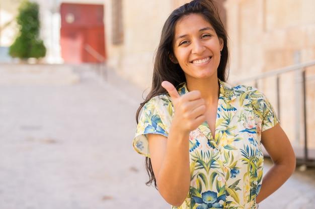 Joven mujer india pulgar arriba en la calle Foto Premium