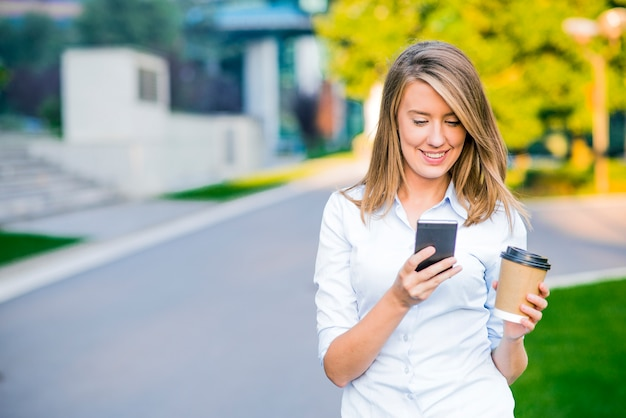Joven mujer inteligente de lectura profesional con teléfono. mujer de negocios de lectura de noticias o mensajes de texto sms en smartphone, mientras que el consumo de café en el descanso del trabajo. Foto gratis