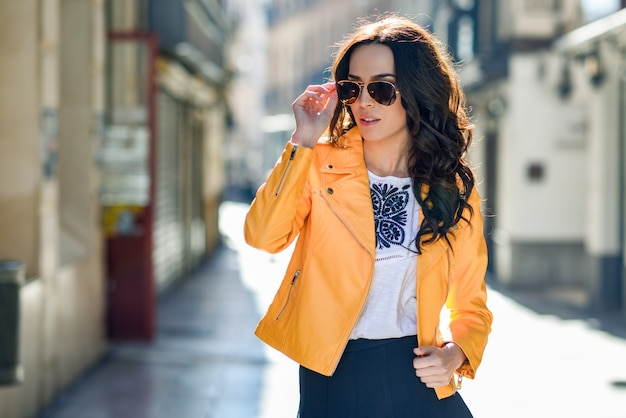 56a2b010b1 Joven mujer morena con gafas de sol en el fondo urbano   Descargar ...