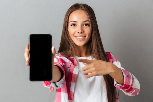 Joven mujer muy sonriente apuntando con el dedo en la pantalla del teléfono Foto gratis