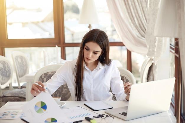 Joven mujer de negocios morena está analizando diagramas y trabajando en la computadora portátil Foto gratis