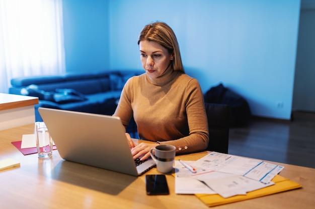 Joven mujer ocupada sentada en casa, usando la computadora portátil y trabajando en un proyecto importante. hay papeles, documentos sobre la mesa. Foto Premium