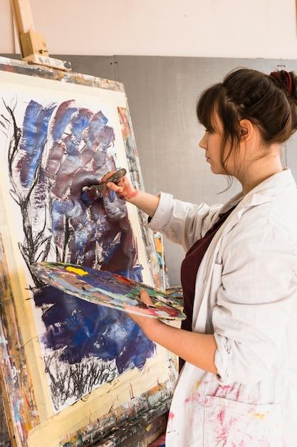 Joven mujer pintando sobre lienzo con pincel Foto gratis