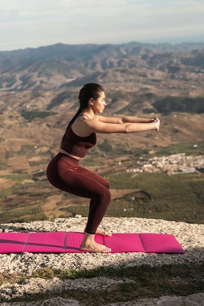 Joven mujer practicando yoga al aire libre Foto gratis