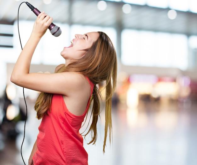 Joven mujer que canta con un micrófono en el fondo blanco Foto gratis