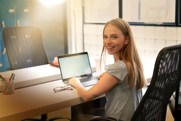 Joven mujer que trabaja en la oficina moderna de inicio Foto Premium