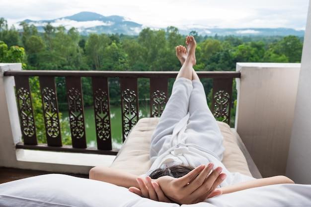 Joven mujer relajarse en la cama y disfrutar de la montaña Foto gratis