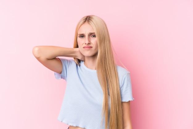 Joven mujer rubia en la pared de color rosa que sufren dolor de cuello debido al estilo de vida sedentario. Foto Premium