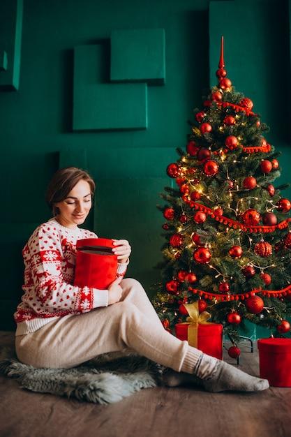 Joven mujer sentada junto al árbol de navidad con cajas rojas Foto gratis