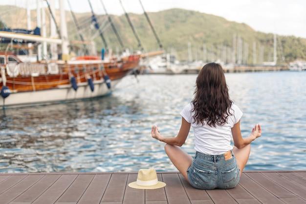 Joven mujer sentada en la orilla de un puerto Foto gratis