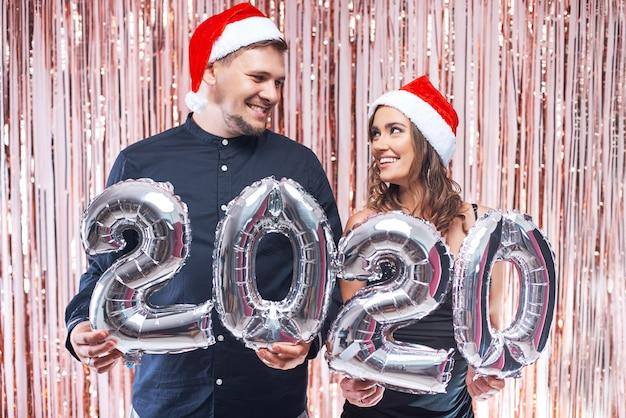 Joven y mujer con sombreros rojos de santa divirtiéndose con 2020 globos metálicos. Foto Premium