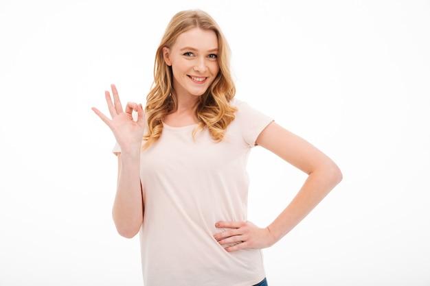 Joven mujer sonriente mostrando gesto bien. Foto gratis