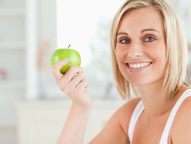 Joven mujer sosteniendo una manzana verde mirando a cámara ... c1b91f7b9a1e