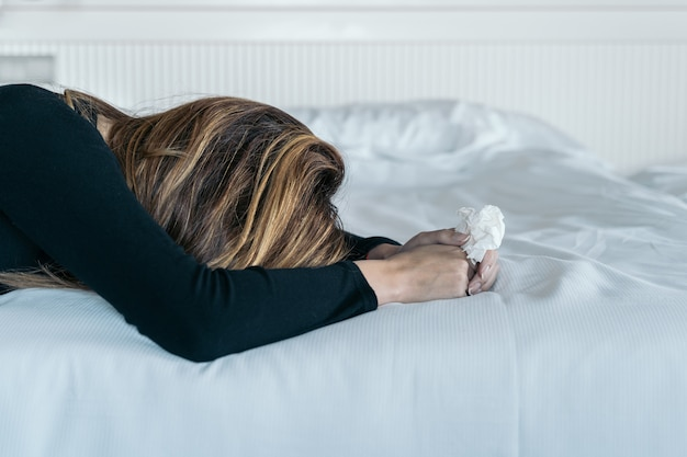 Joven mujer sosteniendo un pañuelo para secar sus lágrimas en su cama. concepto de violencia y maltrato a las mujeres. Foto Premium