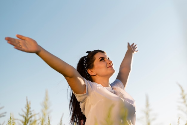 Joven mujer sosteniendo sus brazos en el aire y mirando al cielo Foto gratis
