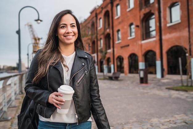 Joven mujer sosteniendo una taza de café. Foto gratis