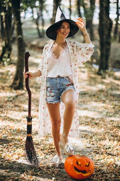 Joven mujer vestida con sombrero con escoba en halloween en el bosque Foto gratis