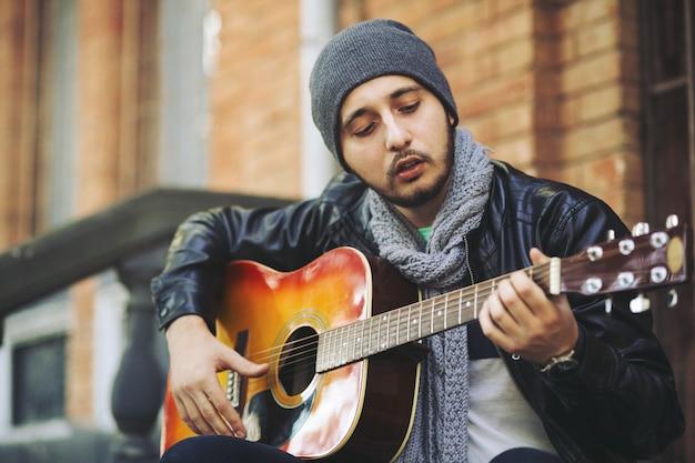 Joven músico con guitarra en la ciudad Foto gratis