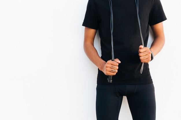 Joven negro en negro con cuerda de saltar Foto gratis