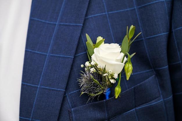 Un joven o novio en una camisa blanca, pajarita y chaleco a cuadros azul o chaqueta. hermoso boutonniere de rosas blancas y hojas verdes en un chaleco de bolsillo o solapa. tema de la boda Foto Premium