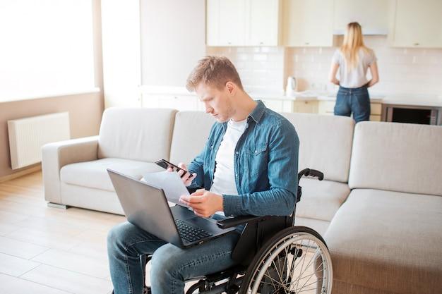 Joven ocupado con discapacidad sentado en silla de ruedas. sostenga la computadora portátil sobre las rodillas. mujer joven de pie detrás y cocinar. luz del día en la habitación. Foto Premium