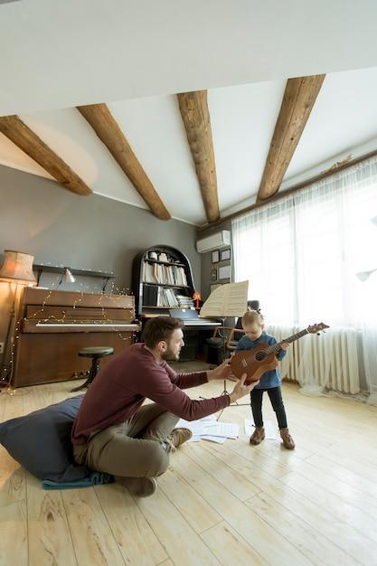 Joven padre enseñando a su pequeña hija a tocar la guitarra mientras está sentado en el piso de la habitación Foto Premium