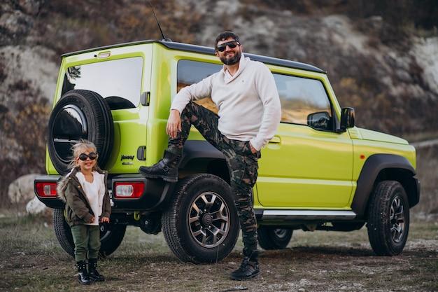 Joven padre de moda con su pequeña hija divirtiéndose en el coche Foto gratis