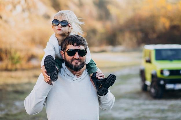 Joven padre de moda con su pequeña hija sentada sobre los hombros Foto gratis