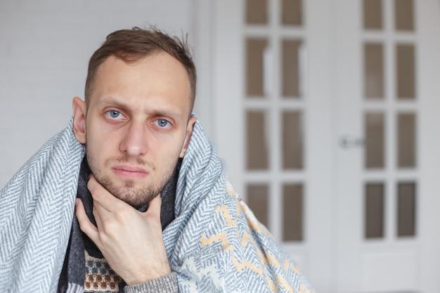 Joven con pañuelo, se cubrió la cabeza con una manta, se agarra el cuello por dolor de garganta Foto Premium