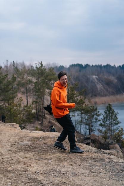Joven parado al borde de un acantilado Foto gratis