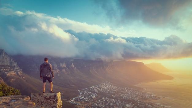 Joven parado en el borde en la cima de la montaña lion's head en ciudad del cabo con una hermosa vista del atardecer Foto Premium