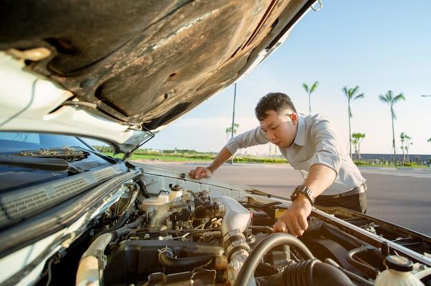 Joven parado frente a su auto roto y abrió el capó para revisar el motor Foto Premium