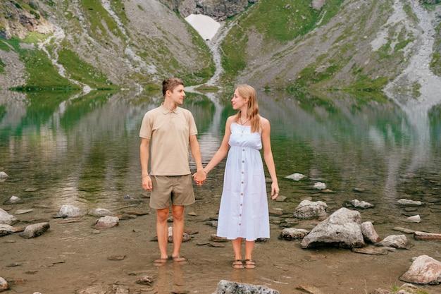 Joven pareja amorosa abrazando en el lago frío entre altas montañas en día de verano. Foto Premium