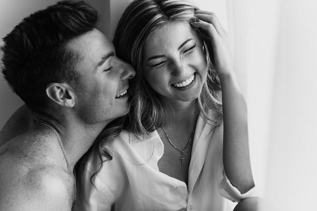 Joven pareja amorosa feliz sonriendo. joven pareja de enamorados diviértete en la víspera de año nuevo o el día de san valentín. foto en blanco y negro de pareja joven Foto Premium