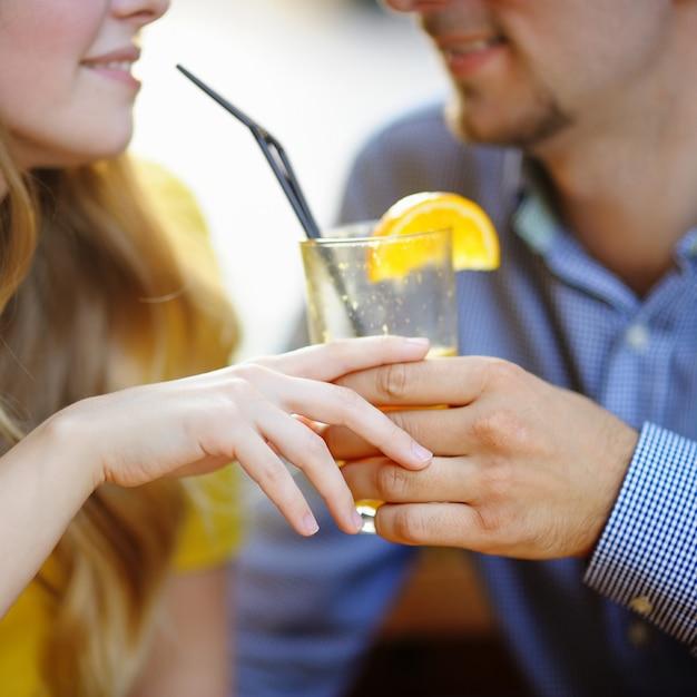 Joven pareja amorosa con vaso de jugo de naranja Foto Premium