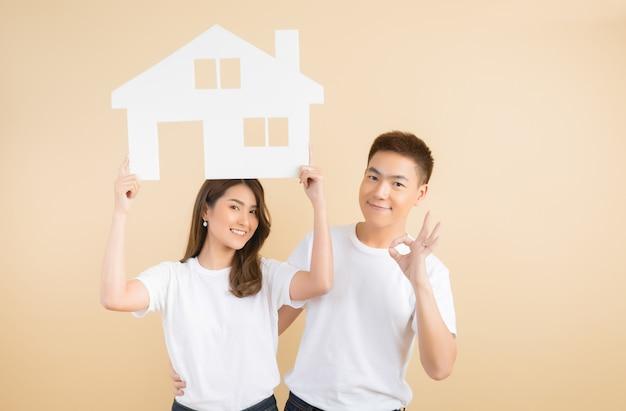 Joven pareja asiática feliz presentando los símbolos de la casa Foto gratis