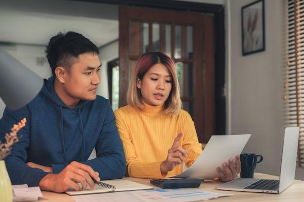 Joven pareja asiática que maneja las finanzas, revisando sus cuentas bancarias usando una computadora portátil Foto gratis