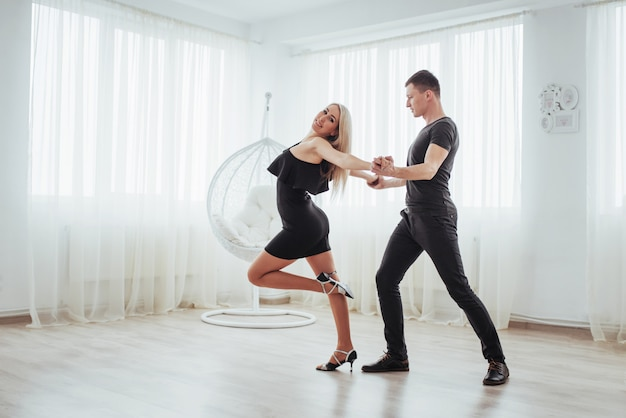 Joven pareja bailando música latina: bachata, merengue, salsa. dos elegancia posan en sala blanca Foto Premium