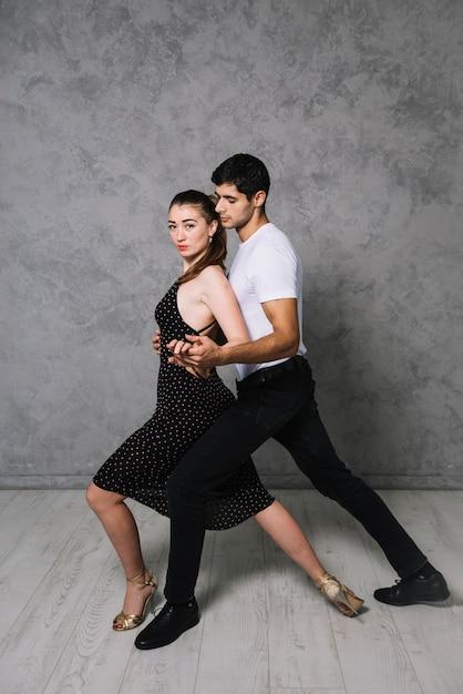 Joven pareja de baile bailando el tango Foto gratis