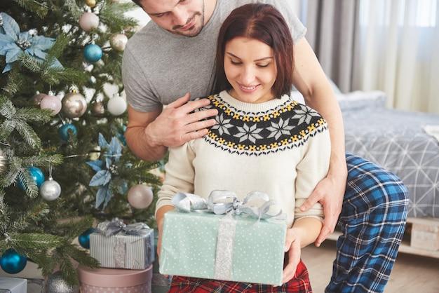 Joven pareja celebrando la navidad. un hombre de repente presentó un regalo a su esposa. el concepto de felicidad y bienestar familiar. Foto Premium