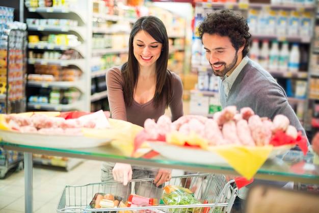 Joven pareja de compras en un supermercado Foto Premium