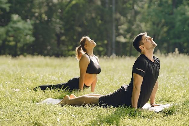 Joven pareja deportiva haciendo yoga fitness. personas en un parque de verano. Foto gratis