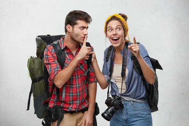 Joven pareja de dos excursionistas equipados con accesorios turísticos y mochilas que disfrutan de un viaje de aventura: un hombre con barba que hace shh con el dedo, pidiéndole a su excitada novia que se calle Foto gratis