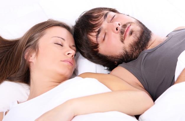 Joven pareja duerme en la cama Foto gratis
