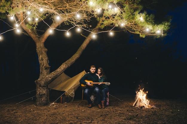 Joven pareja de enamorados acampando turistas sentados junto a un fuego contra una carpa en el bosque con una guirnalda retro, foto con mucho ruido, enfoque selectivo Foto Premium
